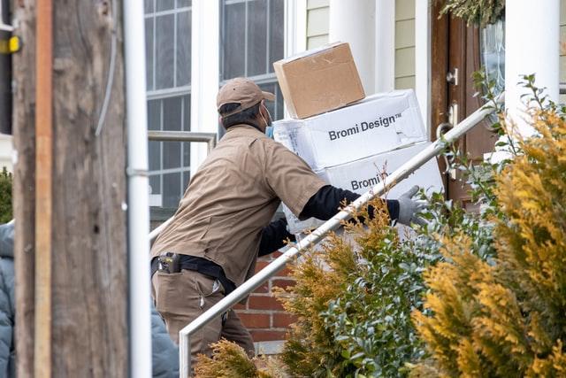 שליח מניח קופסאות משלוח על מפתן דלת
